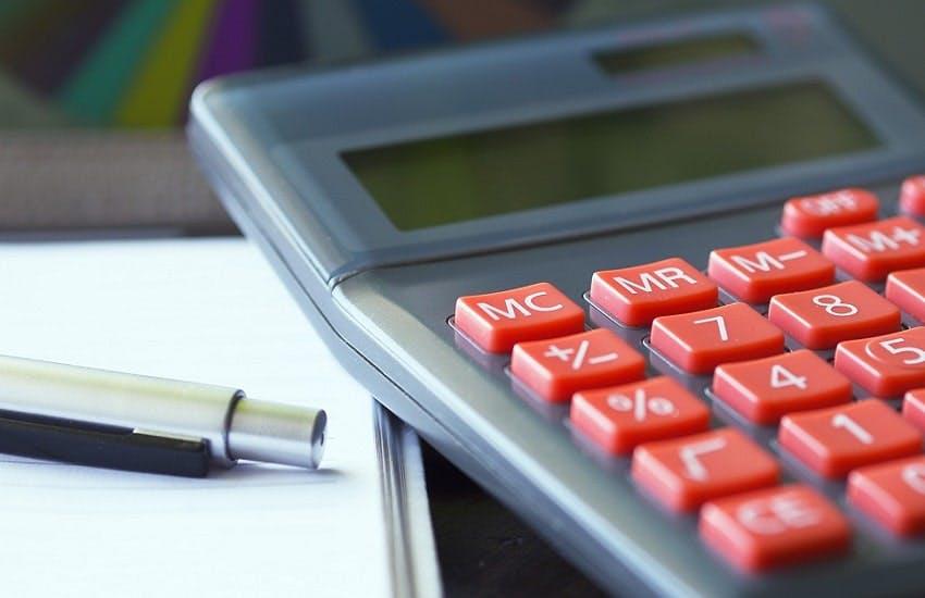 calculatrice à côte d'une feuille blanche et d'un stylo