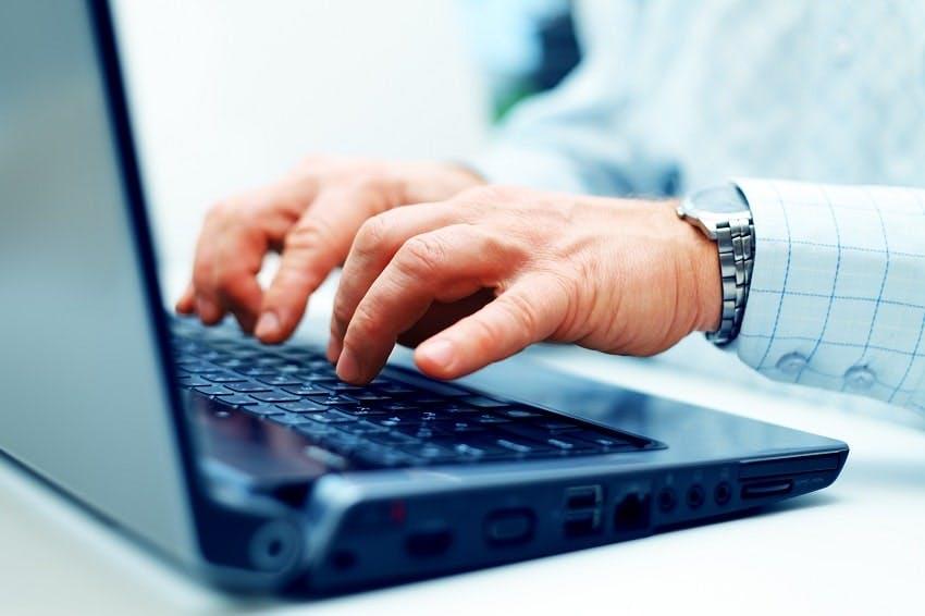 deux mains d'homme qui tape sur un ordinateur portable