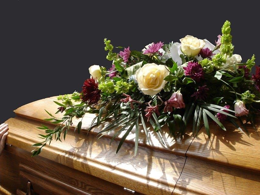 cercueil en bois avec fleurs de deuil