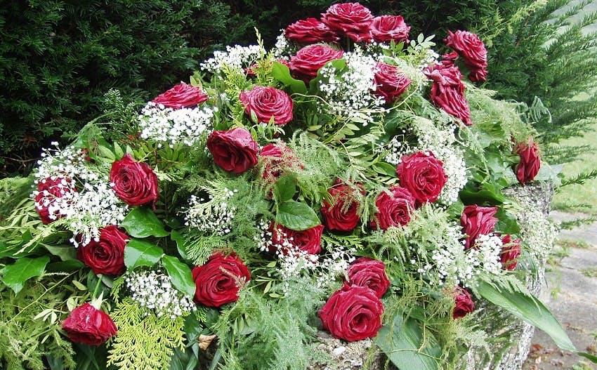 composition florale funéraire avec des roses rouges, du feuillage et des petites fleurs blanches