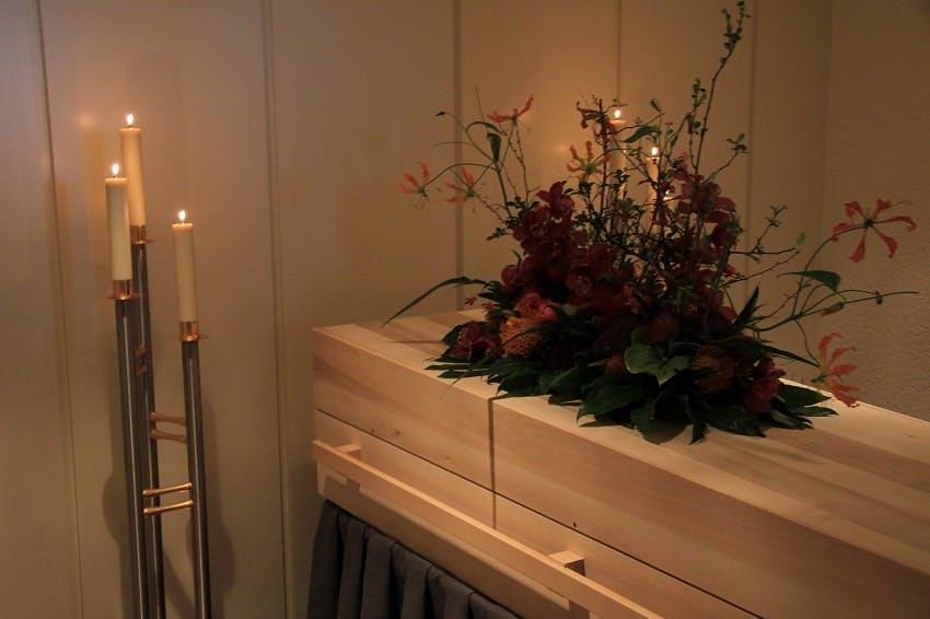 cercueil en bois dans une chambre funéraire avec fleurs et bougies allumées à côté