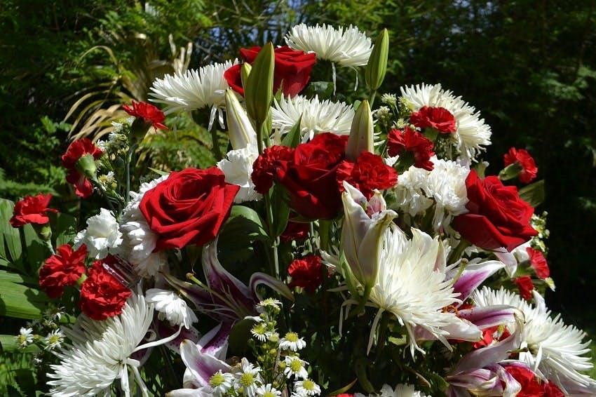 bouquet de deuil avec des roses rouges et des fleurs blanches