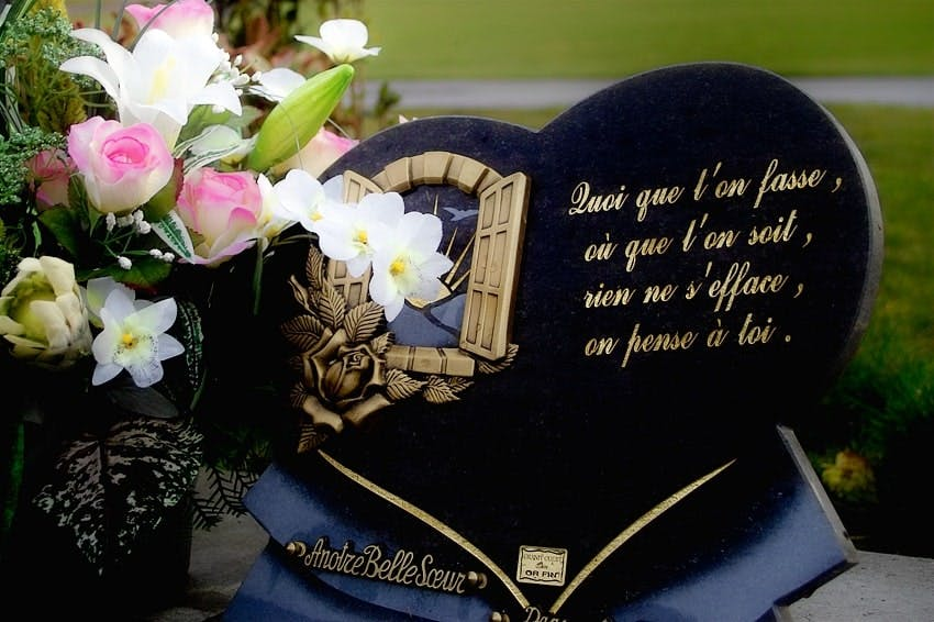 plaque funéraire noire en forme de coeur avec des fleurs sur le côté