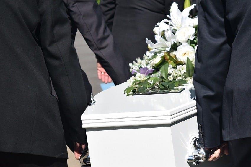 des porteurs qui tiennent un cercueil blanc avec des fleurs blanches