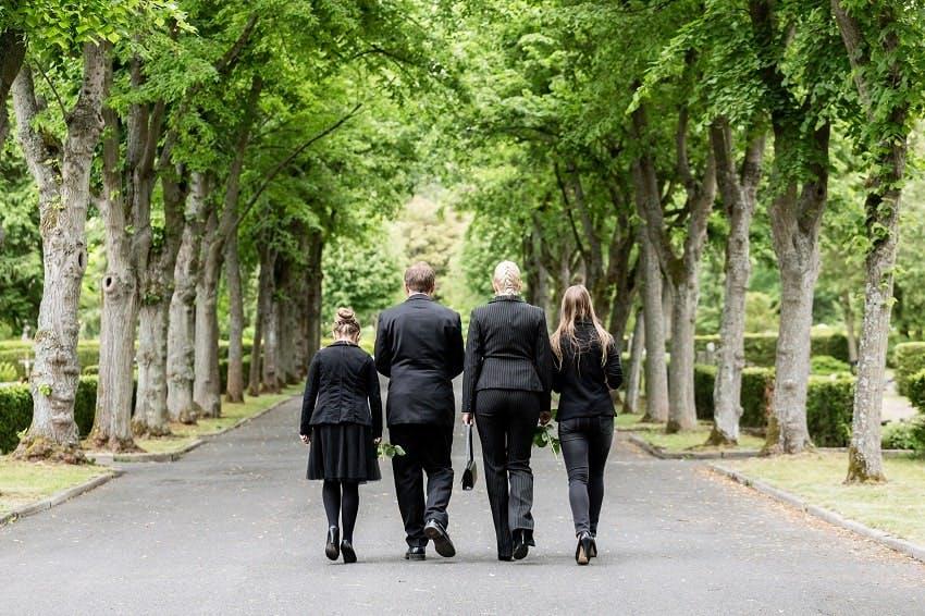deux adultes et deux enfants habillés en noir dans l'allée d'un cimetière