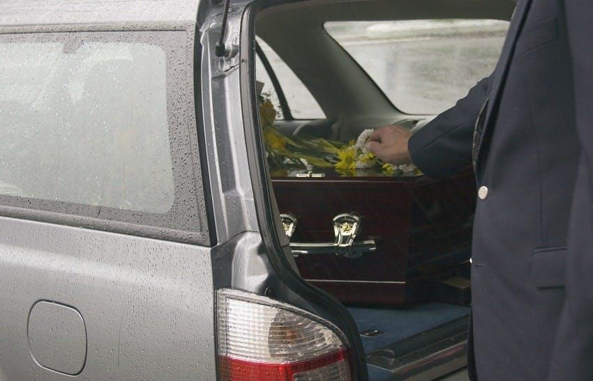 corbillard avec cercueil sous la pluie
