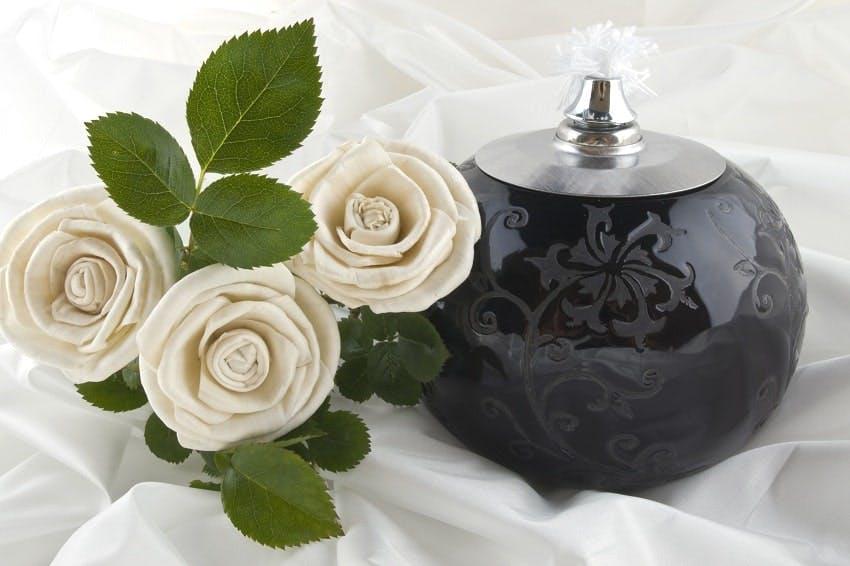 urne funéraire noire posée sur tissu blanc à côté de laquelle sont posées trois roses blanches