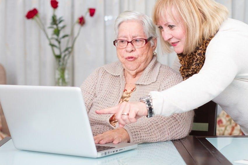 femme montrant l'écran d'un ordinateur à une personne plus âgée