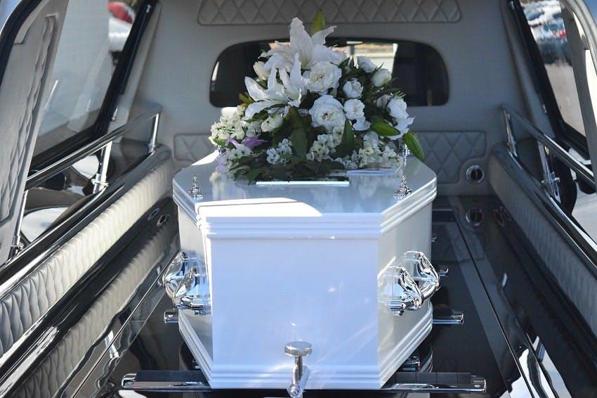 cercueil blanc dans un corbillard avec un coussin de fleurs blanches d'obsèques