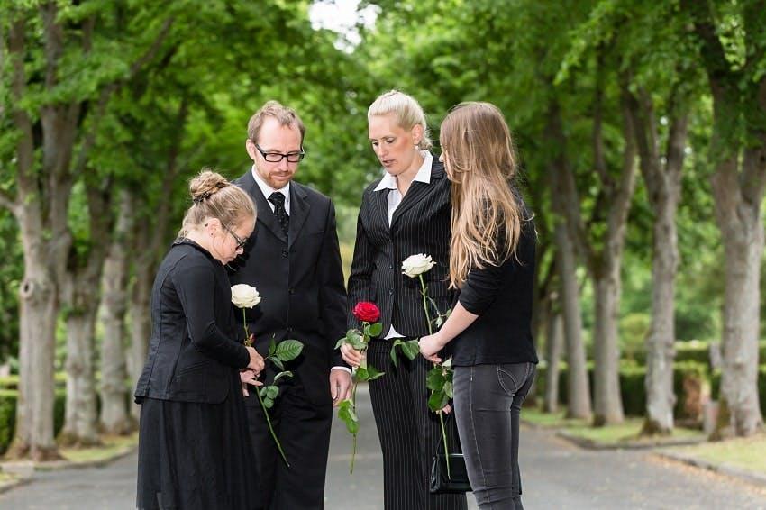 deux adultes et deux enfants tenant des roses rouges et blanches dans un cimetière