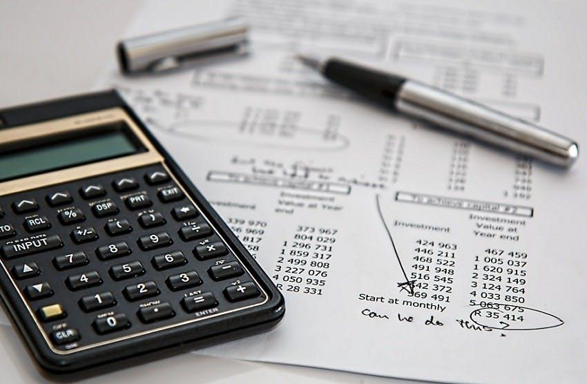 calculatrice et stylo posés sur un devis funéraire annoté et avec des calculs