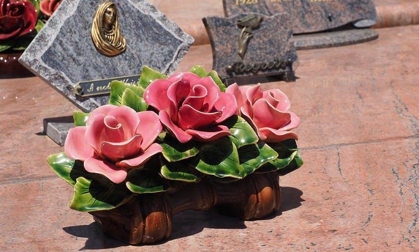 plaque funéraire avec trois roses rouges sur pierre tombale