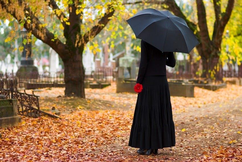 Femme habillée en noir, tenant un parapluie noir ouvert et une fleur rouge dans un cimetière à l'automne