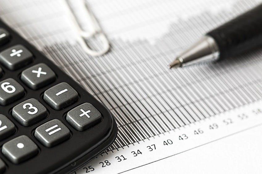 calculatrice et stylo posés sur un devis