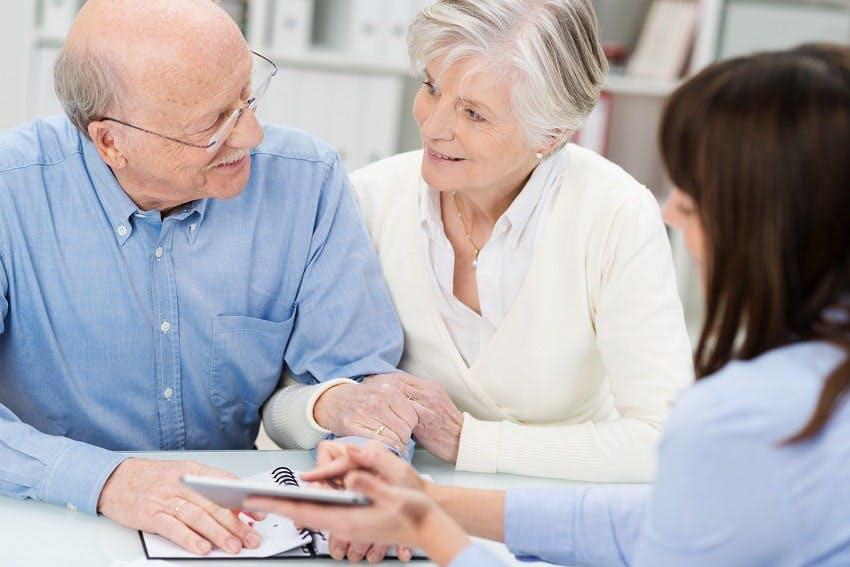 Jeune femme montrant un document à un couple de personnes âgées