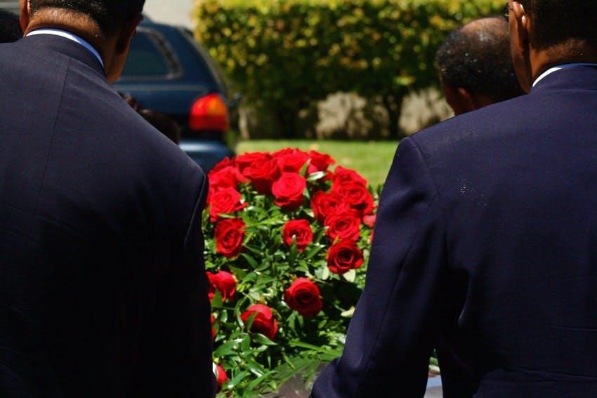 porteur qui tiennent cercueil avec coussin de roses rouges dans cimetière