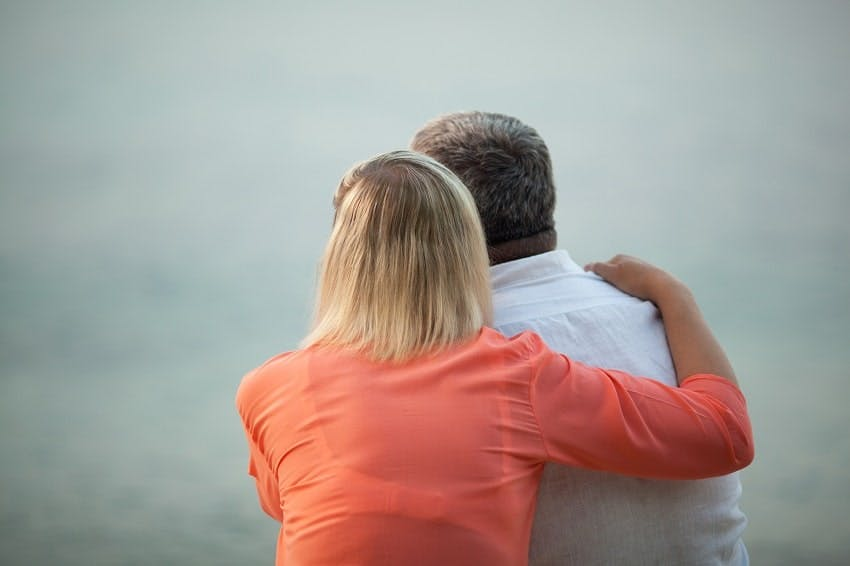 une femme qui a enlacé son mari par l'épaule, vus de dos et regardant dans la même direction que lui
