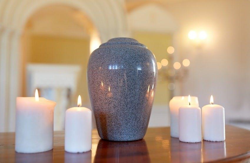 urne funéraire grise posée au milieu de bougies blanches allumées