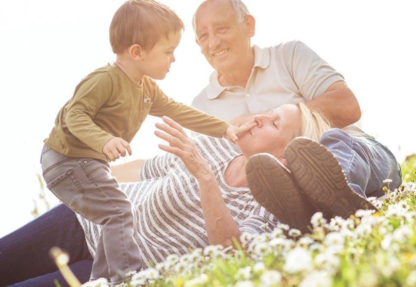 grands-parents jouant avec leur petit-fils sur une pelouse