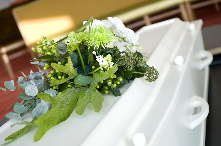 cercueil blanc avec coussin de fleurs blanches et de feuilles vertes