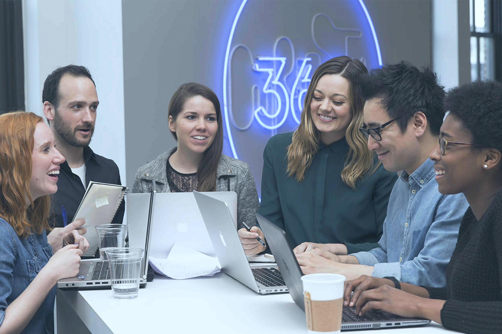 Group of people having a team meeting against the 360i logo