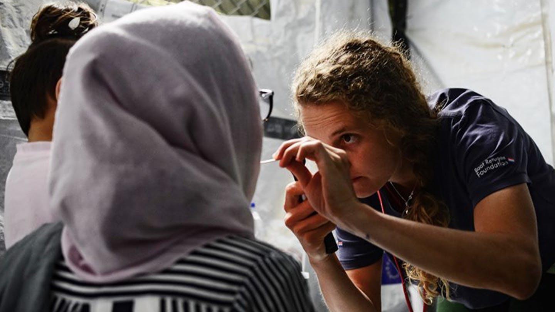 Foto Ärztin nimmt Stäbchenprobe von Frau mit Kopftuch