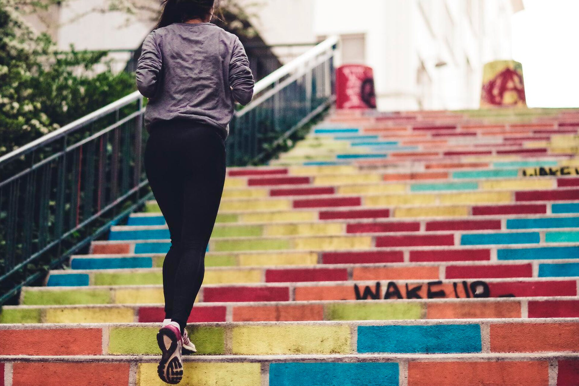 A jogger is walking up colorful stairs