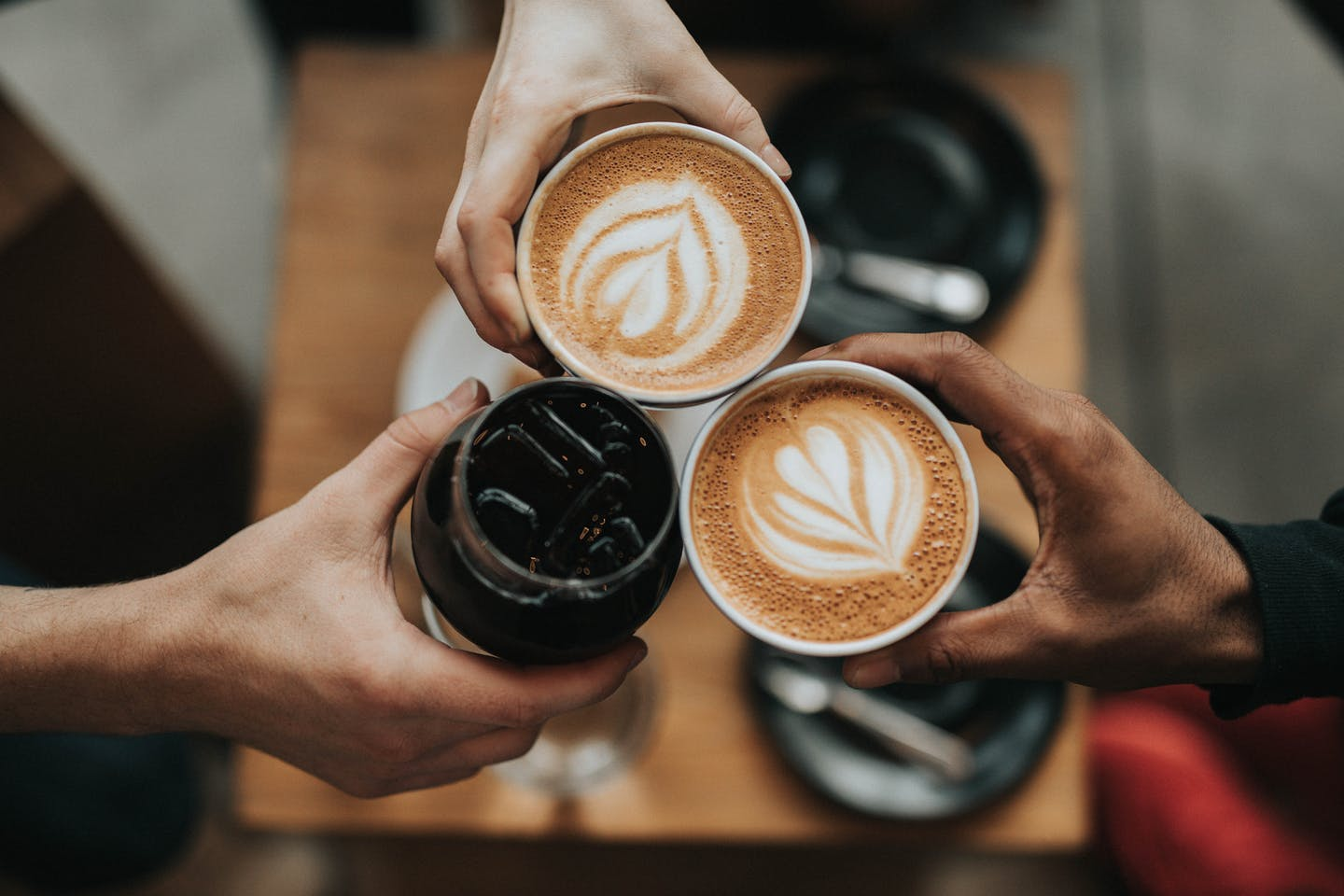 three people holding cups of coffee close together