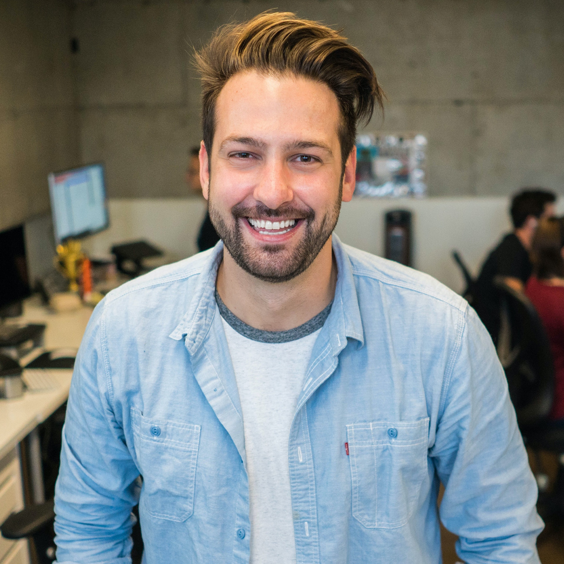 a smiling man standing in an office space