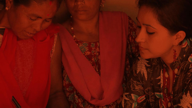 Foto in dunkler Stimmung mit Rotstich von indischen jungen Frauen