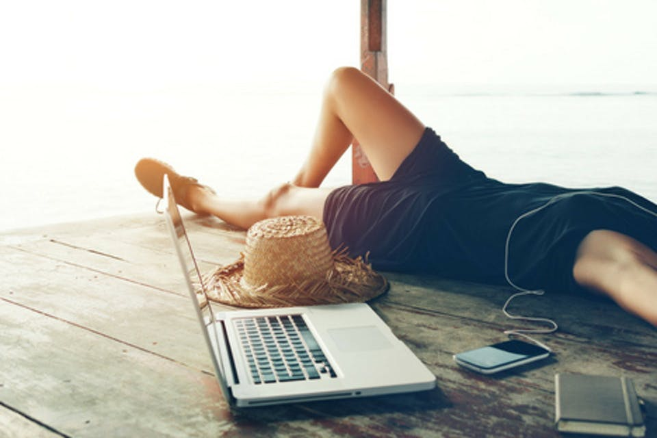 jemand liegt mit seinem Laptop auf einem Steg
