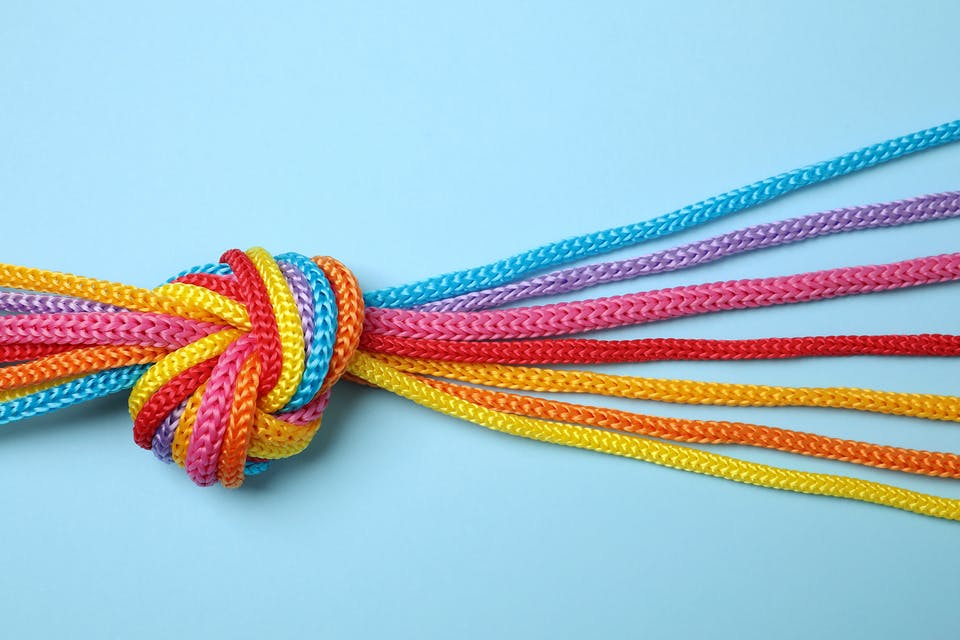 photo of colorful threads tied together to a knot