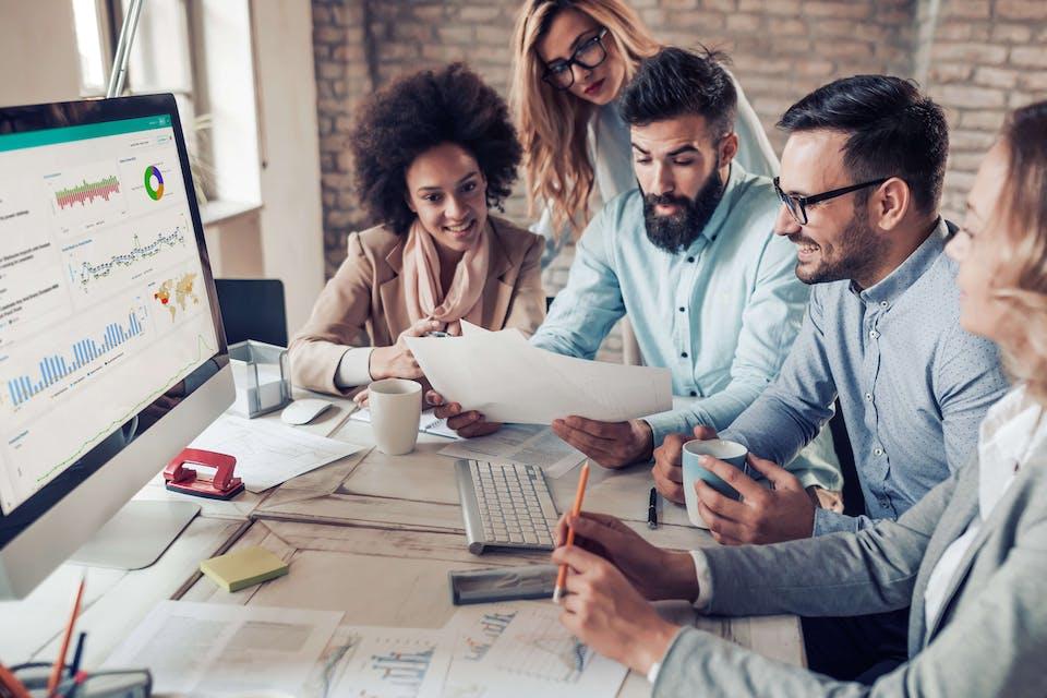 Man sieht eine Gruppe an Menschen gemeinsam an einem Tisch um einen Mac arbeiten. Geöffnet ist das Meltwater Social Media Monitoring Tool mit einem Compare Dashboard.