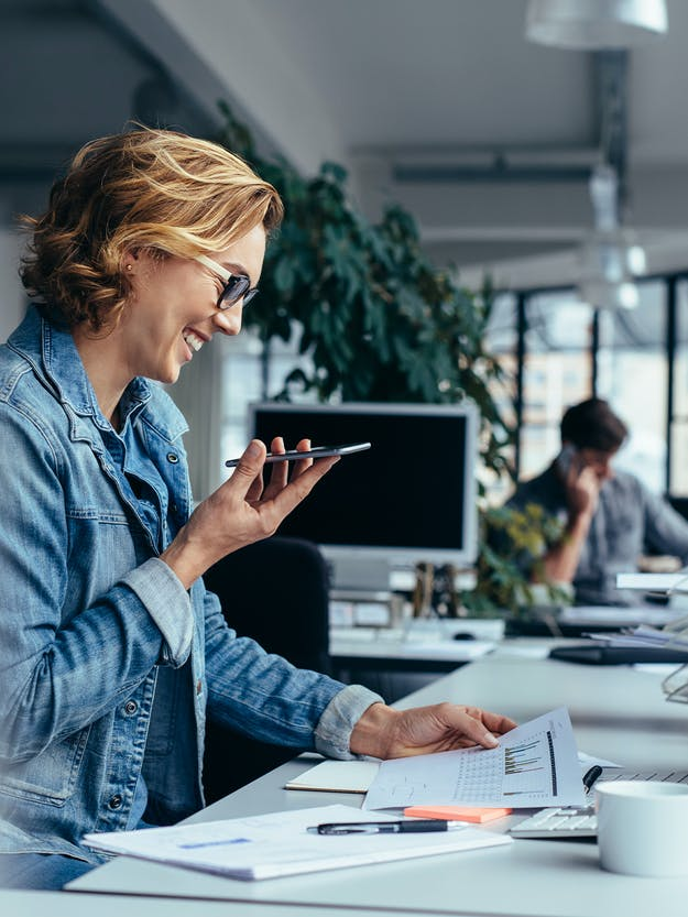 You can see a picture of a woman in the office who is smiling and looking at her smartphone and a paper report