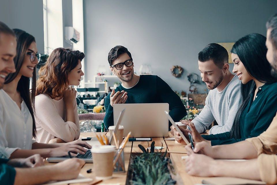 Gruppe an Menschen sitzt im Büro und arbeitet an einem Tisch