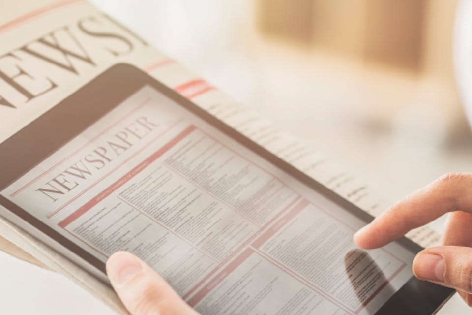 Man holding newspaper and tablet