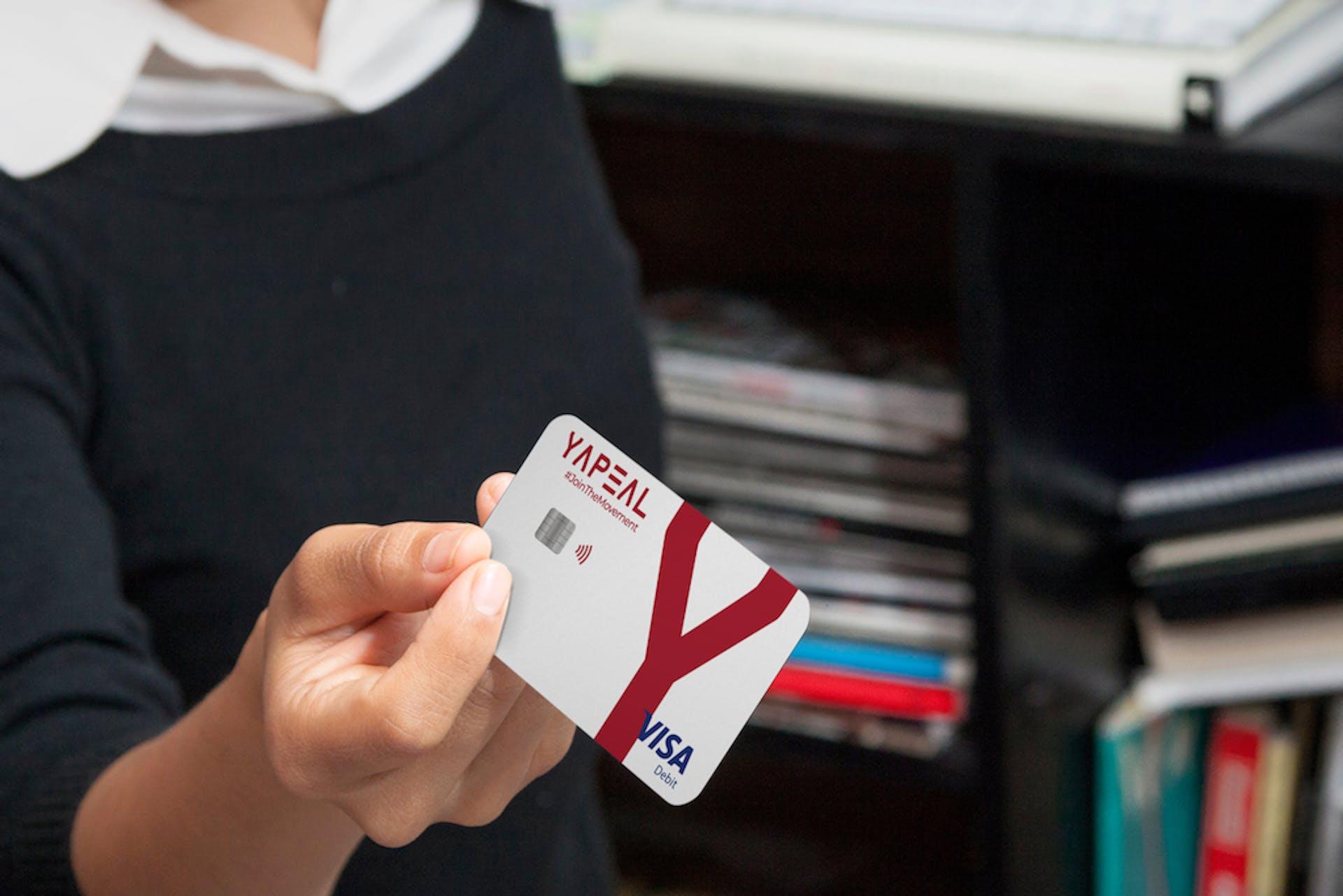 Foto Frau hält YAPEAL Kreditkarte Visa in die Kamera
