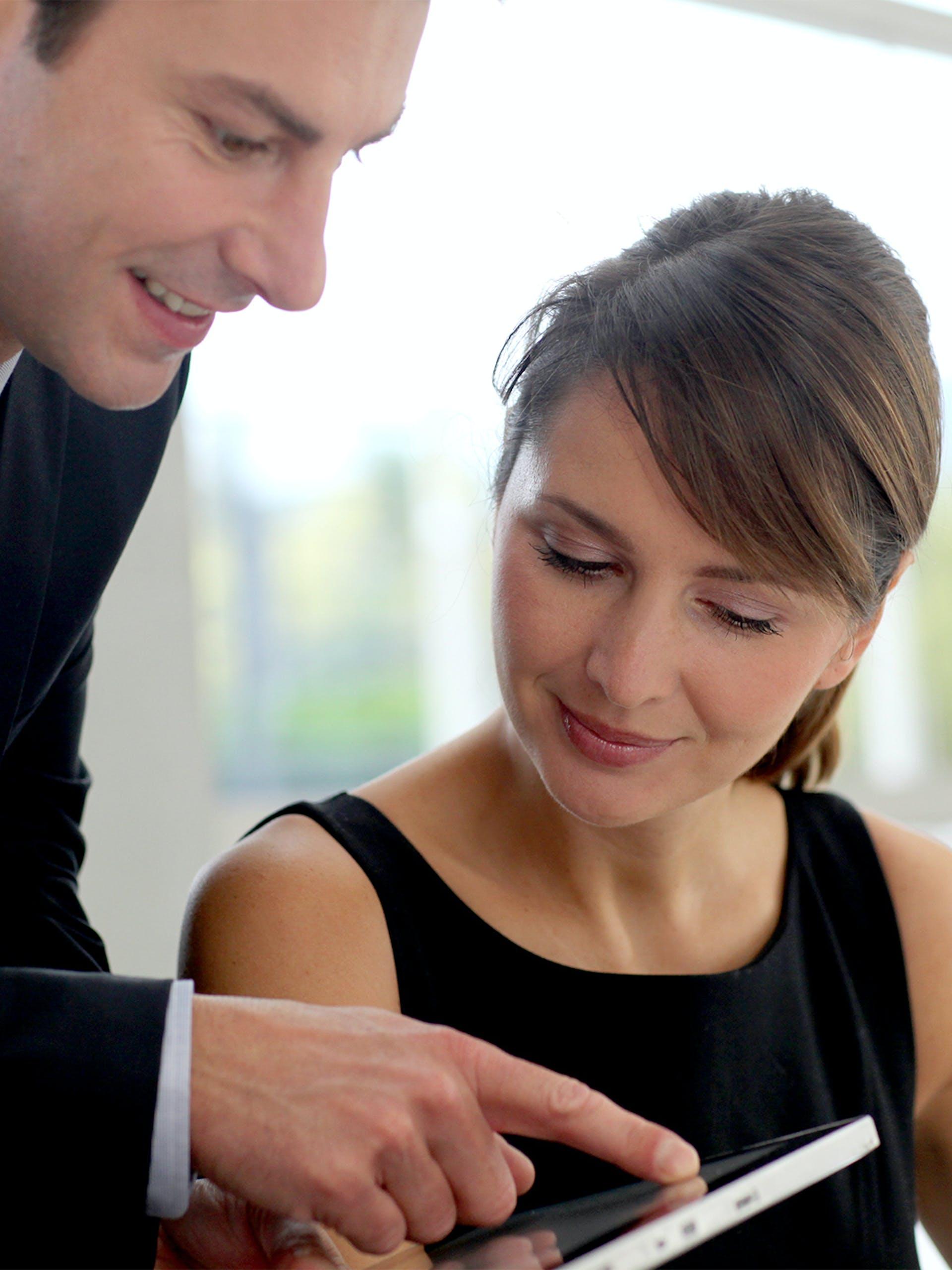 Man and woman looking at tablet.