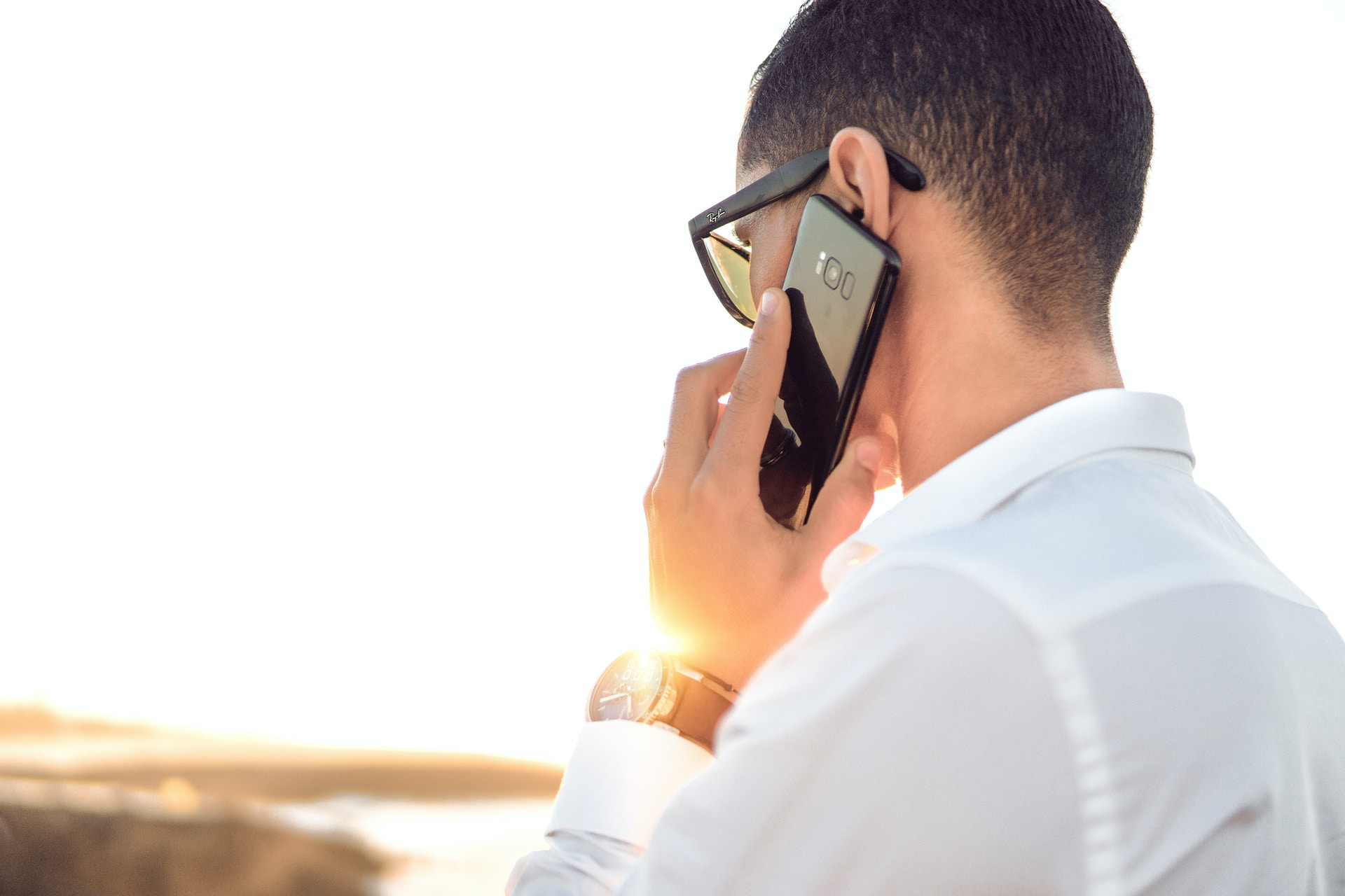 person wearing sunglasses holding a mobile phone to their ear