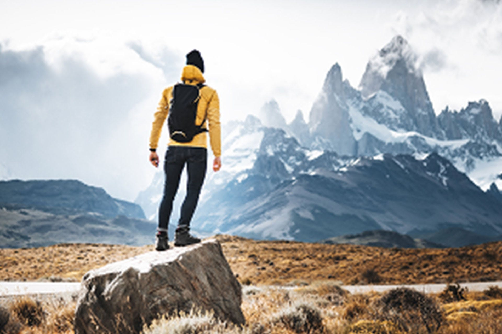 A man standing on a rock looking at a mountain