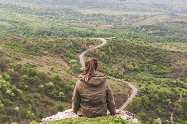 Young woman looking out over winding road. Understanding your customer journey is crucial to successful marketing strategy.