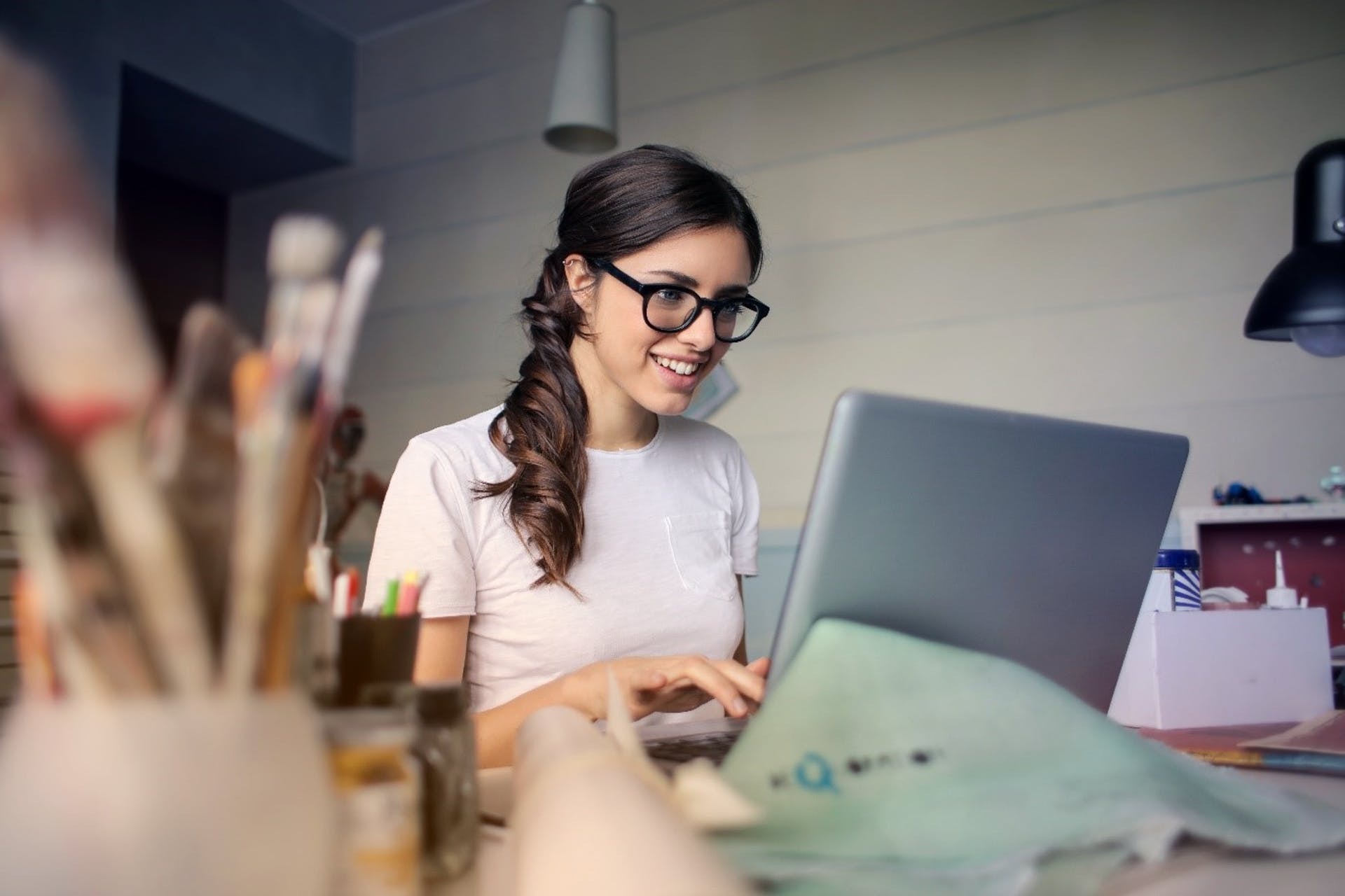 Brunette woman in glasses using her laptop while seated at a desk