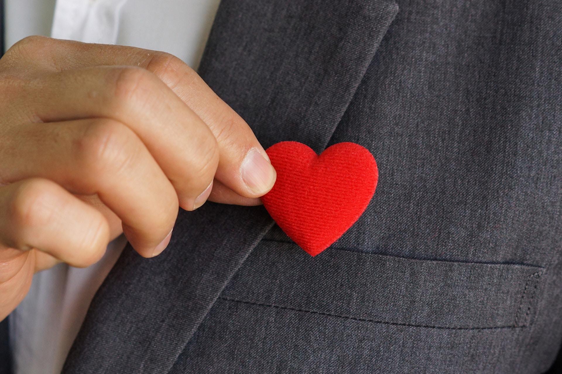 Foto Mann im Anzug hält rotes Stoffherz vor seine Brust als Zeichen für Brand Loyalty, Markentreue und Kundenbindung