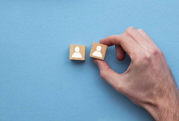 Hand rearranging cubes on blue background