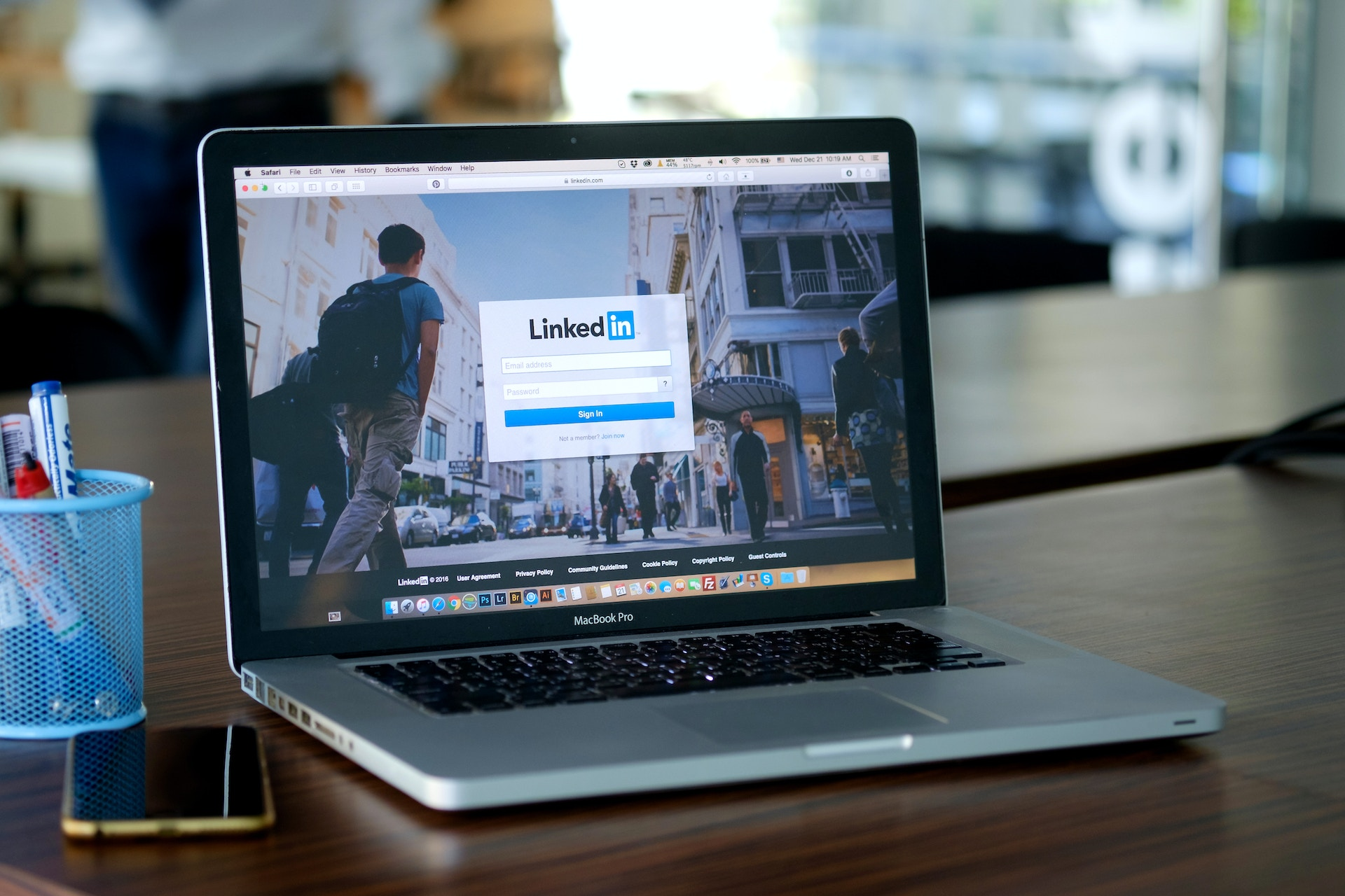 A laptop on a desk with the LinkedIn homepage open