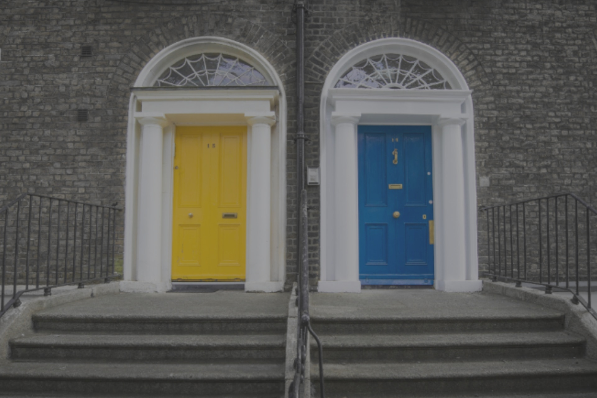 Two doors with grey steps leading up to them. One door is yellow, the other is blue.