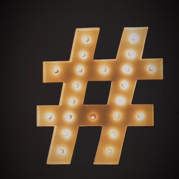 Hashtag symbol light up on black background. Commonly used in strategic social media marketing.