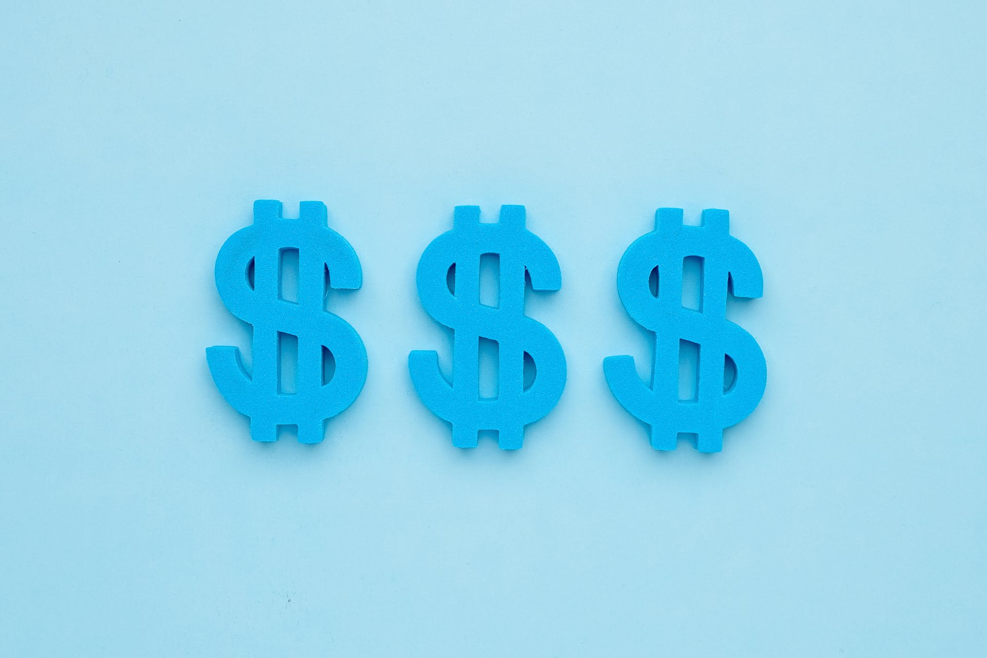 Three blue American dollar signs against a blue background. The dollar signs represent the revenue your marketing team could generate through Facebook lead ads.