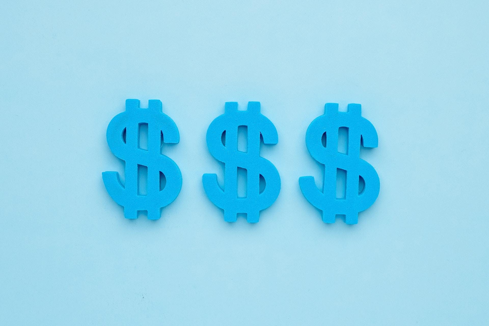 Trois signes de dollar américain bleu sur fond bleu. Les signes dollar représentent les revenus que votre équipe marketing pourrait générer via les publicités Facebook.