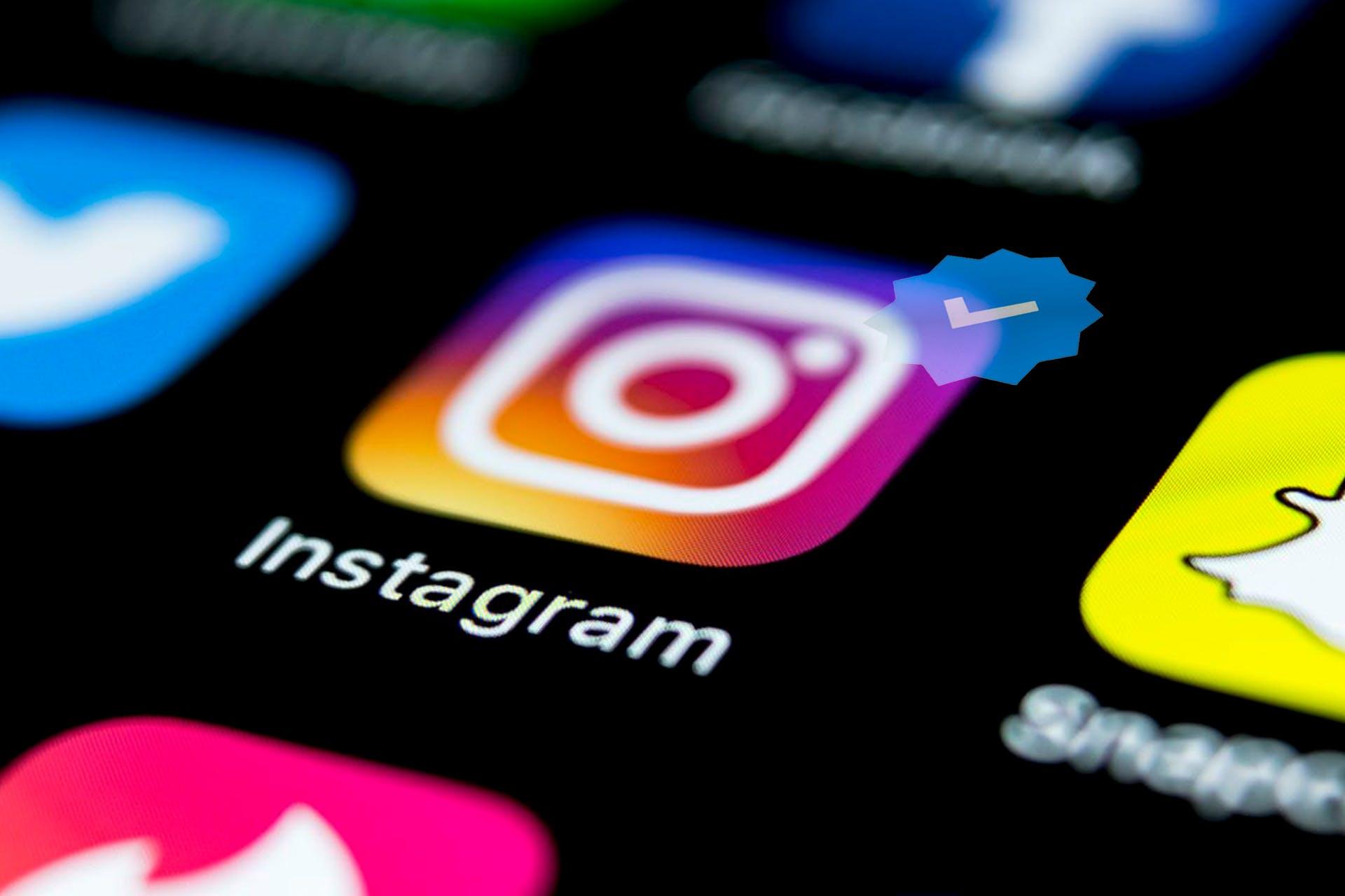 Man sieht das Instagram Icon für die App auf einem Smartphone Screen. Das Icon zeigt den blauen Haken, der auf ein verifiziertes Instagram Konto hinweist. Wir zeigen euch, wie ihr eure Instagram Verifizierung beantragt.